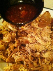 Pouring sauce on shredded chicken